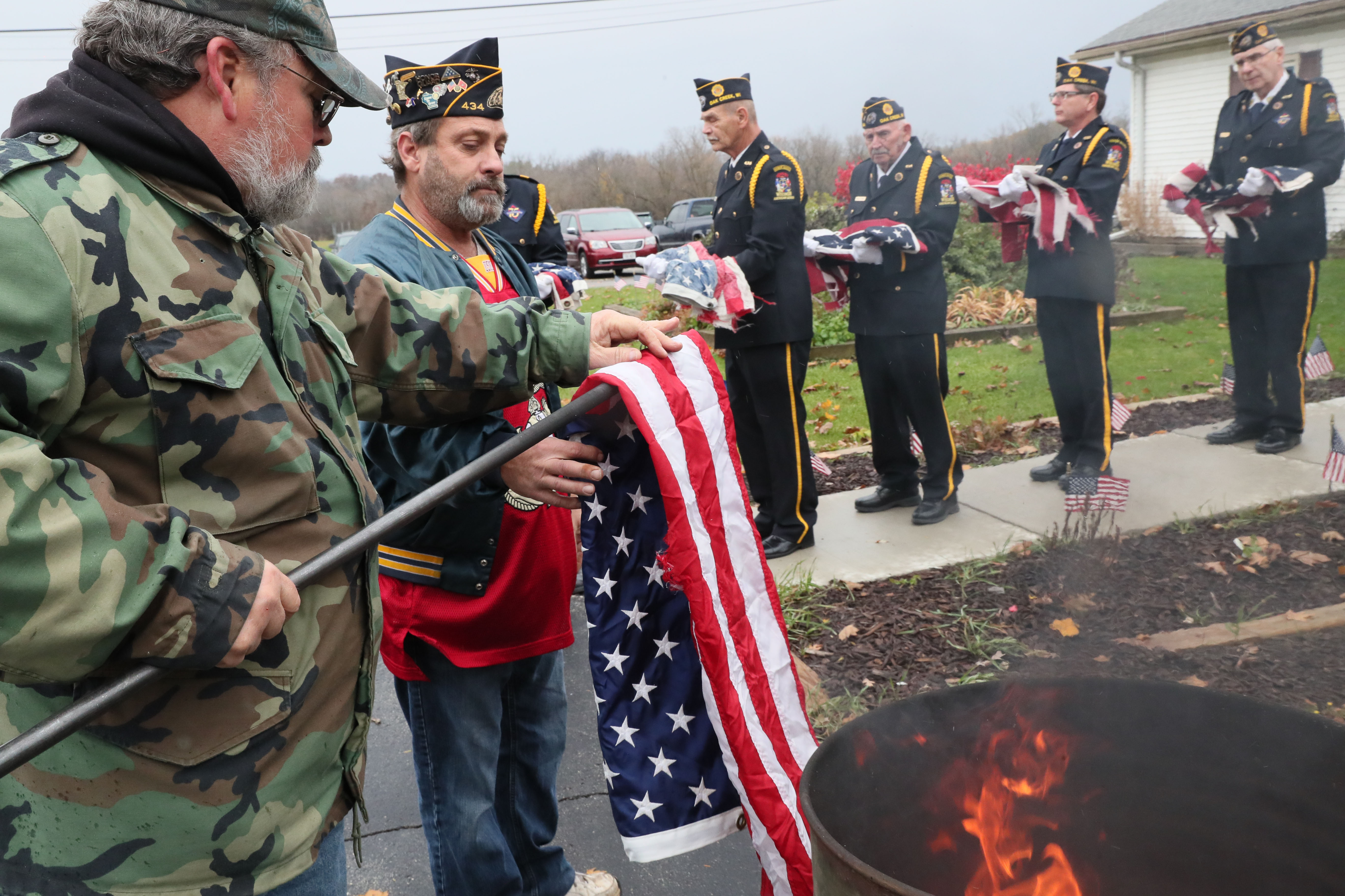 Here Roger Jenson (left) takes flags from Second Vice Commander Scott Zalewski (center) to be placed in the burn barrel. Other members of the honor guard wait at right with flags to be destroyed.  Photo by Michael Sears/Milwaukee Journal Sentinel