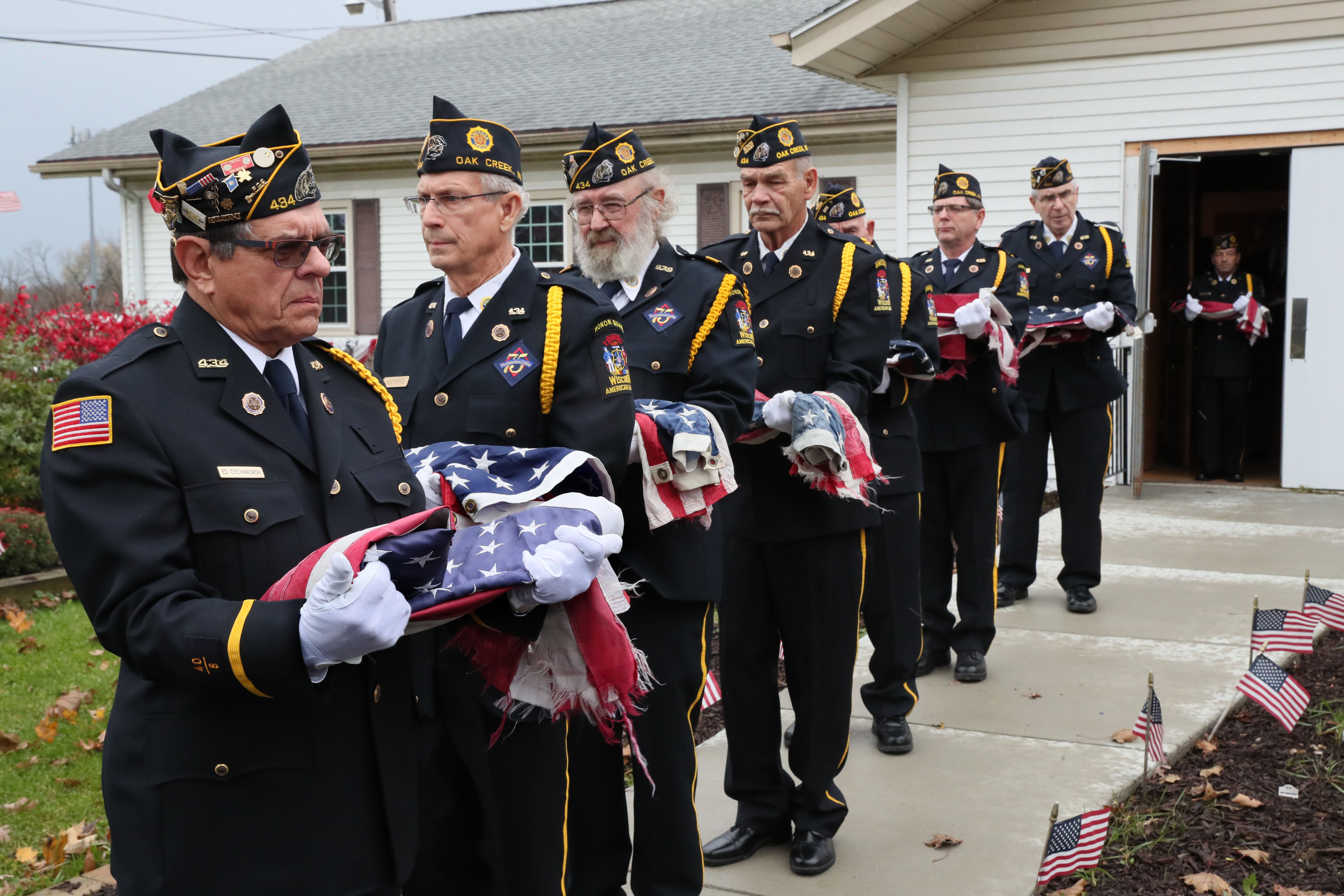 Here Ed Ciechanowski (far left) a member of the honor guard, holds a flag along with others as they make their way toward a fire where the flags will be destroyed.  Photo by Michael Sears/Milwaukee Journal Sentinel