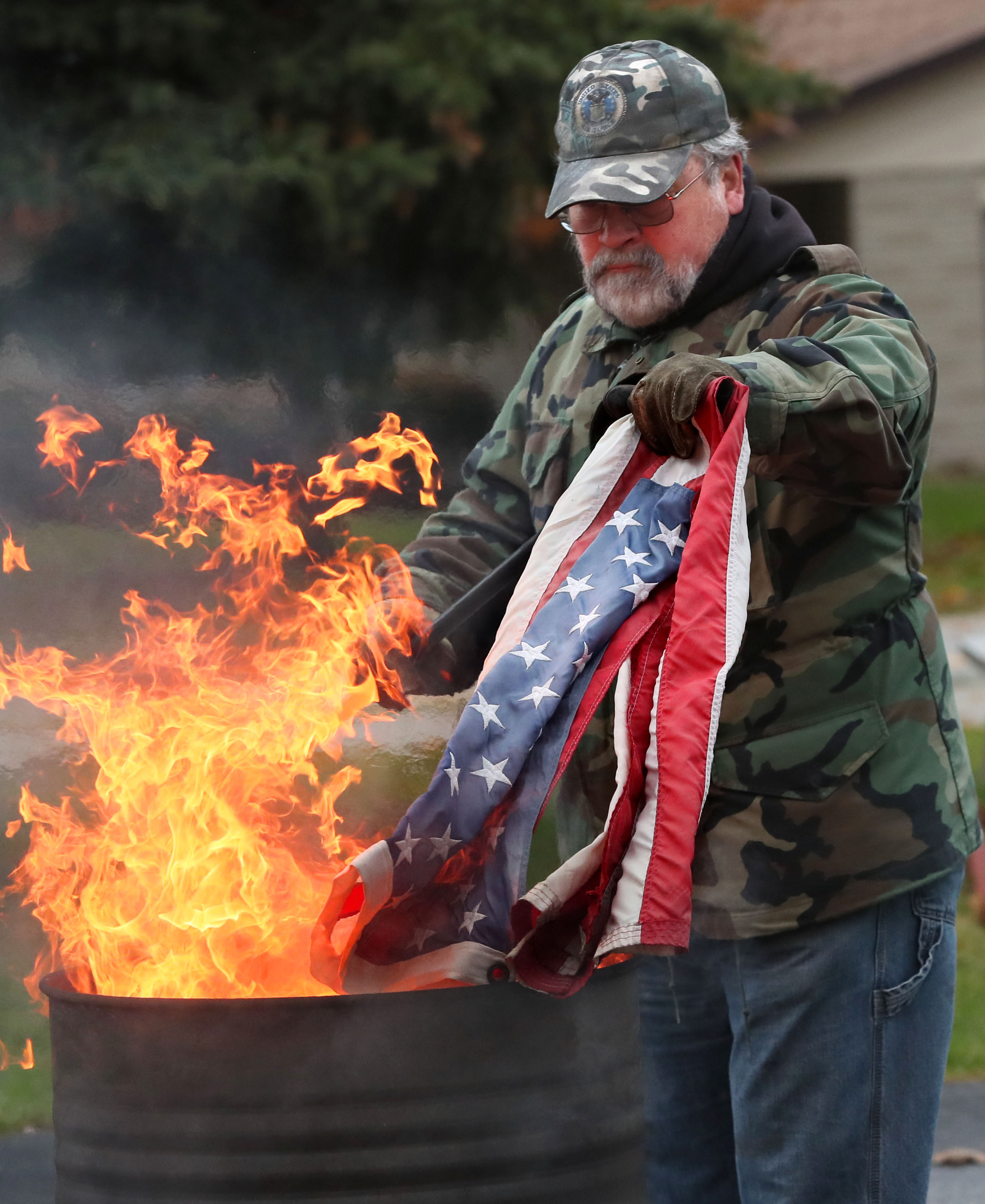 Here post member Roger Jenson, lowers a flag to be destroyed into the flames. Photo by Michael Sears/Milwaukee Journal Sentinel